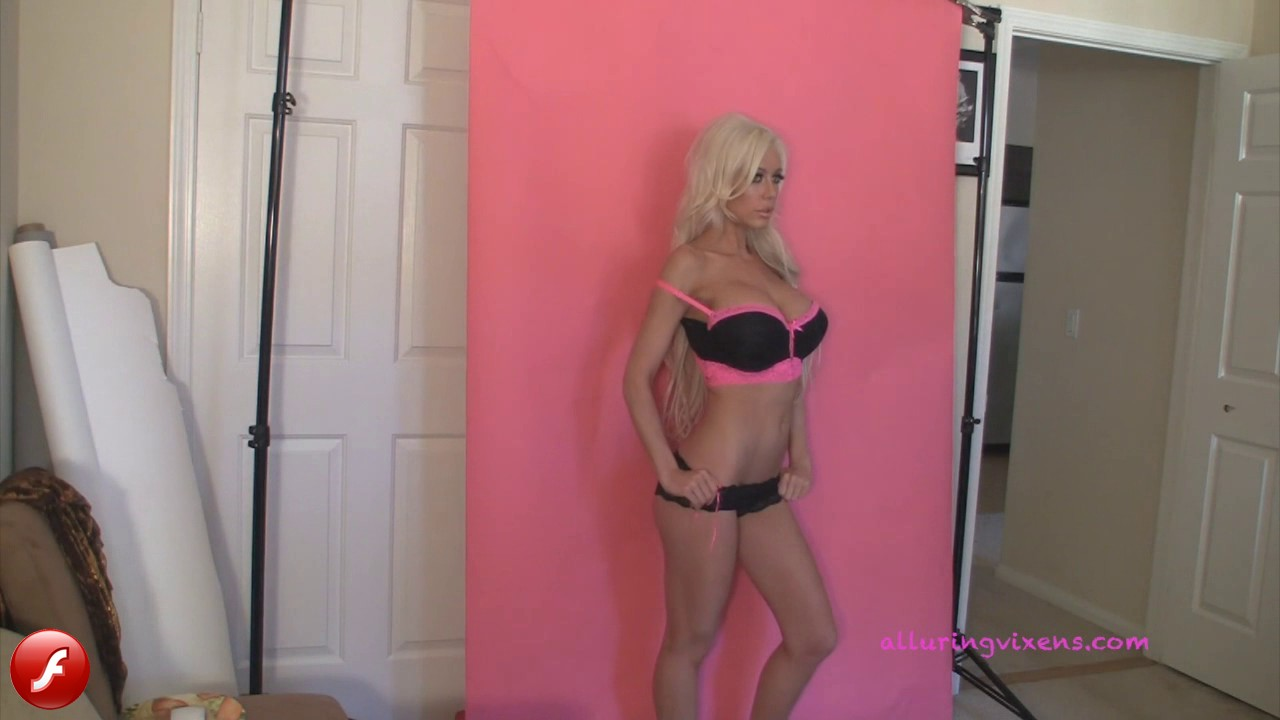 Watch as busty blonde Alluring Vixen babe Karly shows off her perfect curves in a pink and black lace bra and matching panties